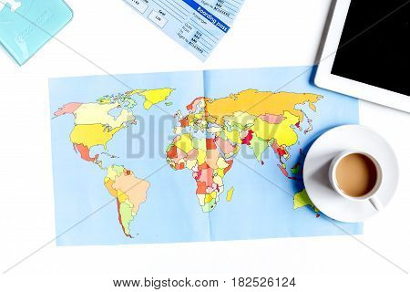 traveller set with cup of coffee, tablet and map in vacation design on white table background top view