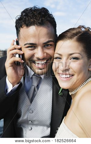Multi-ethnic bride and groom with cell phone