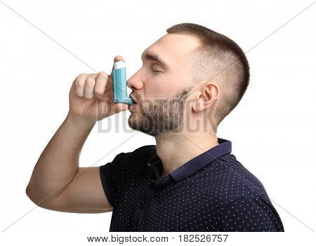 Young man using asthma inhaler on white background