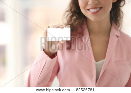 Beautiful African American woman with business card on blurred background, closeup