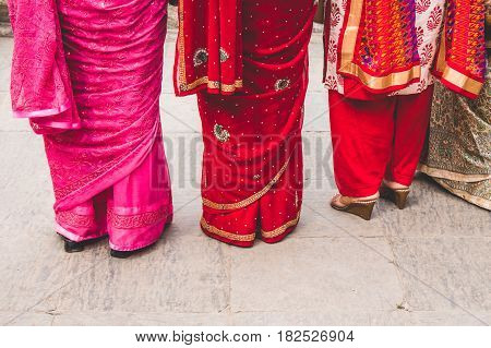 Three women dressed in colourful saris. Abstract composition looking down.
