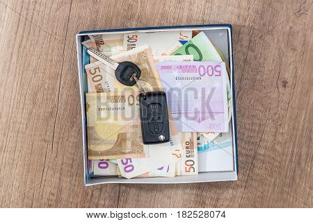 Euro Banknote With Car Key In Box On Desk