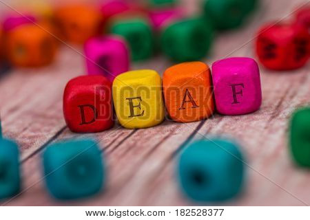 Deaf - Word Created With Colored Wooden Cubes On Desk.