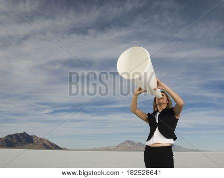 Hispanic businesswoman yelling into megaphone