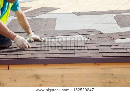 Construction worker putting the asphalt roofing (shingles) on a new frame house