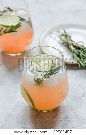 vegetable smoothie with lime pieces and fresh rosemary in glass on stone table background