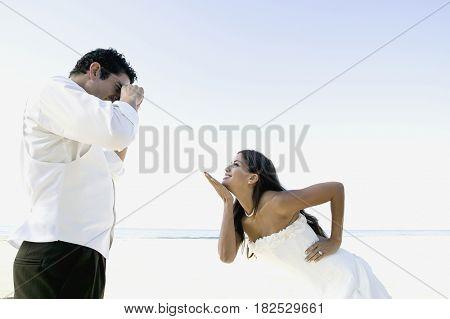 Hispanic groom taking photograph of bride
