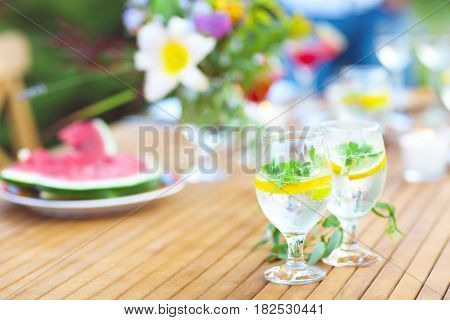 Two glasses of natural lemonade on the table at summer outdoor party