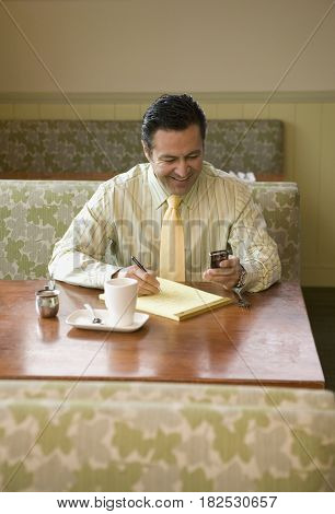 Hispanic man in coffee shop checking messages