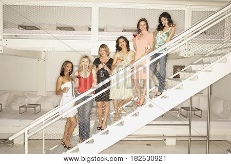 Multi-ethnic women with cocktails on stairs