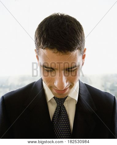 Hispanic businessman looking down