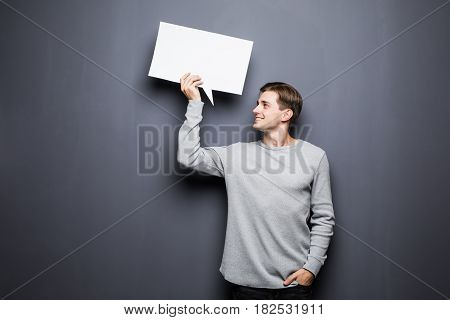 Young Man Holding White Blank Speech Bubble With Space For Text And Look At It Isolated On Grey Back