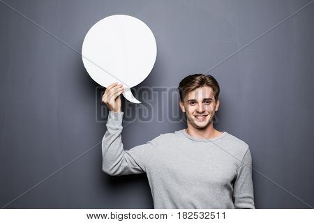 Portrait Of Young Man Holding White Blank Speech Bubble With Space For Text Isolated On Grey Backgro