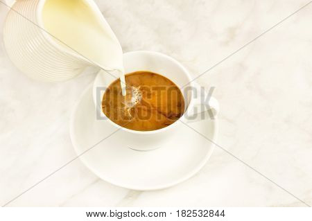 A photo of milk poured into a cup of coffee, with a place for text