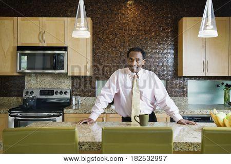 African businessman standing in modern kitchen