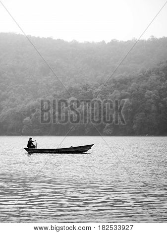 A woman alone in a canoe boat paddling on Fewa Lake Pokhara on a misty morning in black and white. Pokhara Nepal.