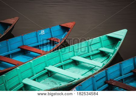Colourfully painted wooden canoes lined up by the lakeside in Pokhara Nepal.