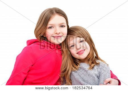 Portrait of two cute smiling girls isolated on white background