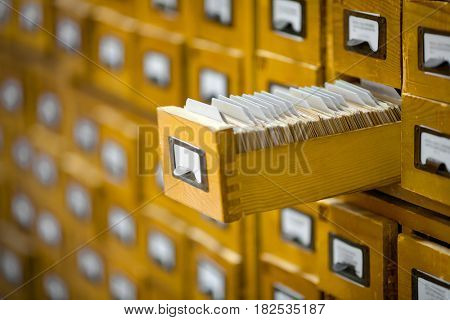 yellow library or archive reference catalogue with opened card drawer.