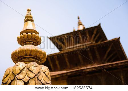 Close up detail of the top of a stupa decorated with gold and one of the multi leveled pagodas in Patan's Durbar Square Nepal.