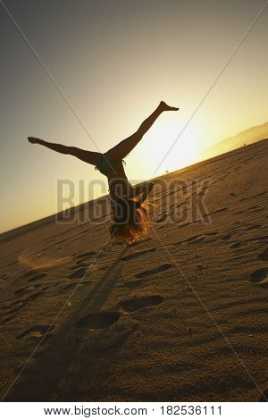 Mixed race woman doing cartwheel on beach