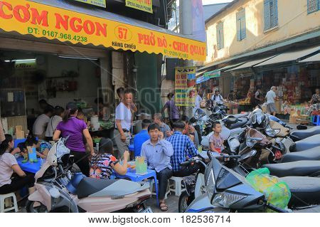 HANOI VIETNAM - NOVEMBER 23, 2016: Unidentified people have breakfast in Old Quarter district.