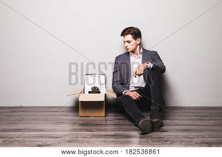 Fired Frustrated Man In Suit Sitting On Floor In Office.
