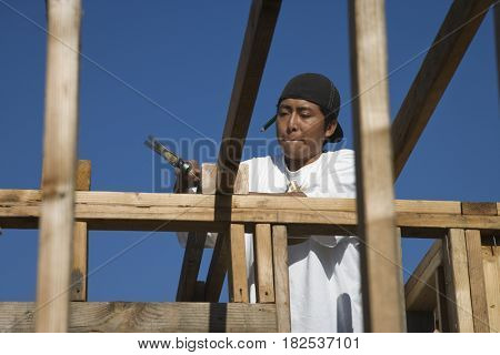 Hispanic construction worker hammering wood