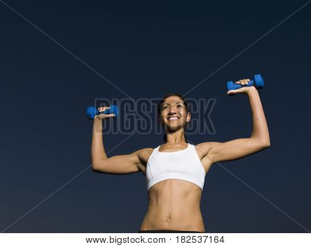 Mixed race woman doing shoulder presses with dumbbells
