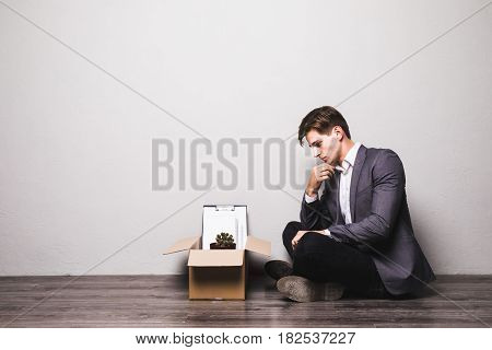 Sad Fired Businessman Sitting At Floor After Being Dismissed At Work In Office