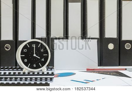Closeup white clock for decorate in 4 o'clock desk of officer with work paper and document file in office room textured background in work concept