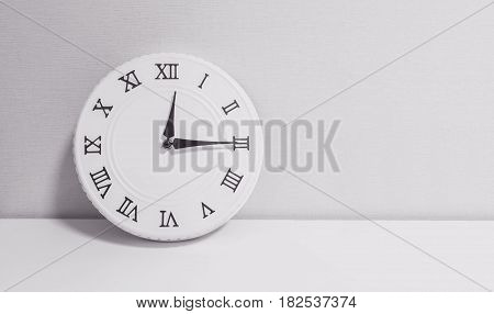 Closeup white clock for decorate show a quarter past twelve o'clock or 12:15 p.m. on white wood desk and wallpaper textured background in black and white tone with copy space
