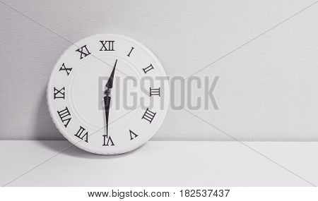 Closeup white clock for decorate show half past twelve o'clock or 12:30 p.m. on white wood desk and wallpaper textured background in black and white tone with copy space