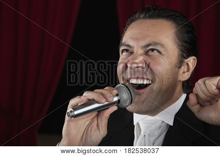 Close up of Hispanic man singing into microphone