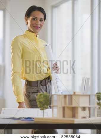 Mixed race architect with blueprints