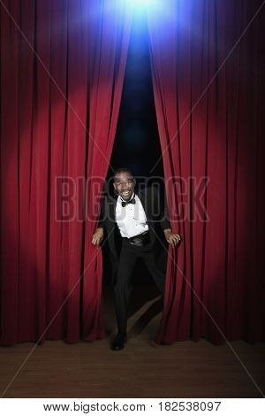 African American man in tuxedo emerging from red curtains