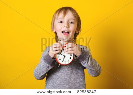 Cute little boy with alarm clock on the yellow background.