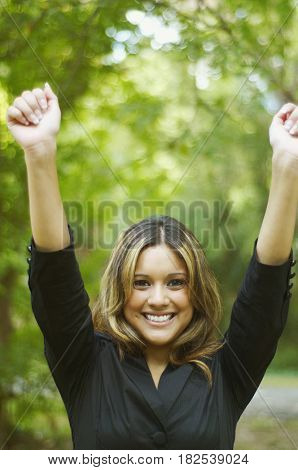Hispanic businesswoman posing with arms raised
