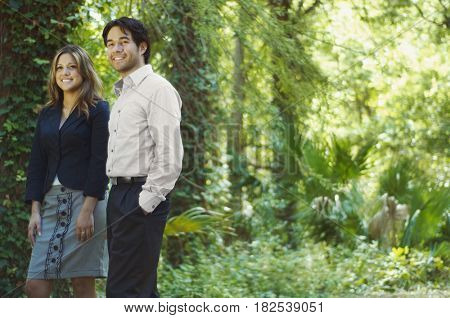 Hispanic business people standing in woods