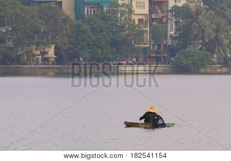 Fisherman at Truc Bach lake cityscape Hanoi Vietnam
