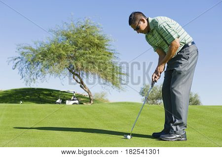 Hispanic man playing golf