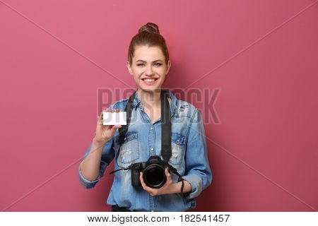 Beautiful photographer with business card on color background