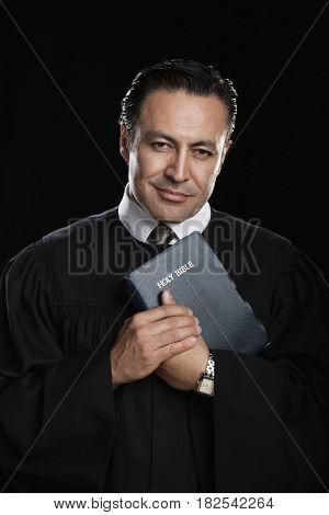 Hispanic preacher posing with Bible
