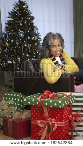 African woman in livingroom with Christmas gifts