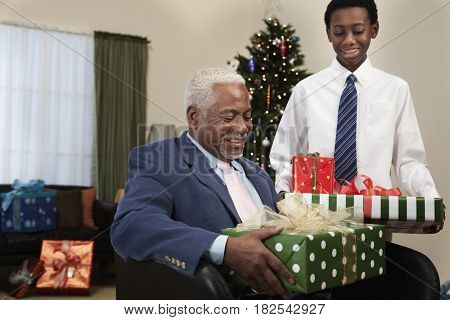 African boy giving grandfather Christmas gifts