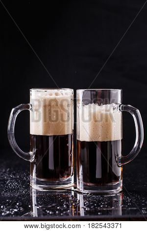 Two beer mugs stand on table at black background
