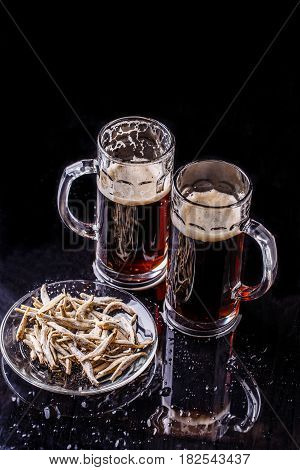 Two mugs of beer, plate of anchovies on black table
