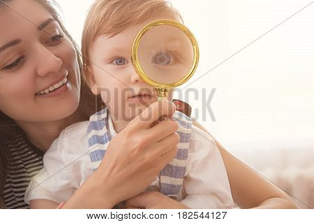 Mom With Her Son Looking Through A Magnifying Glass. Little Boy With Magnifying Glass.