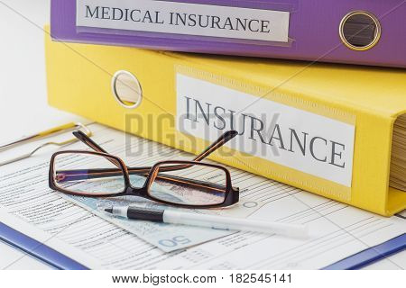 Clean Insurance Form, Folders, Pen And Glasses