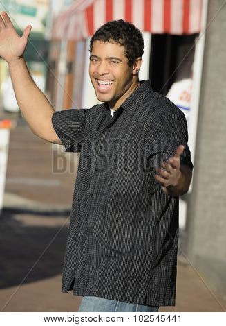 Mixed race man on urban street with arms outstretched
